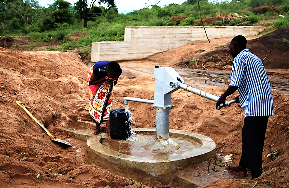 Two local people fetching water using a hand pump from a closed well near a sand dam
