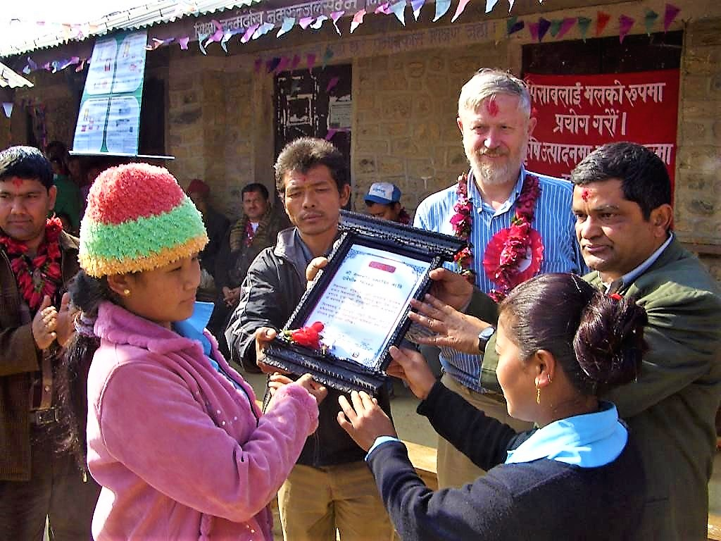 "Community members from a small village in Nepal receive an award for achieving the ""open defecation free status"" after a successful CLTS Campaign. Source: KROPAC (2009)"