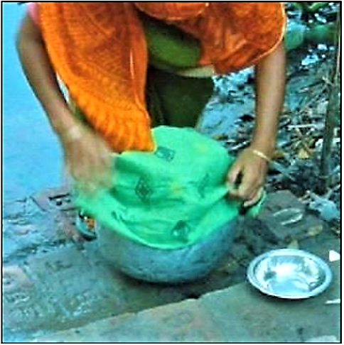 UNKNOWN (n.y): A woman uses a sari cloth to strain water