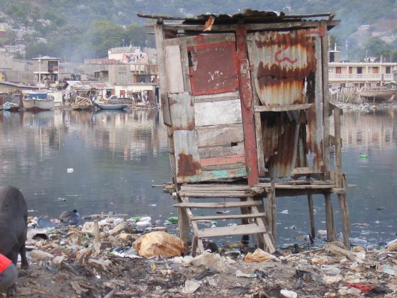 An overhung latrine in Port Haitien (Haiti). It is hard and unsafe to enter, especially for elder people and children. The contamination of the water body is obvious. Source: AIDG on Flickr (2007)