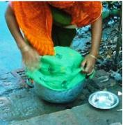 A woman using a sari cloth to strain water. Source: AFRICDAY (2009)