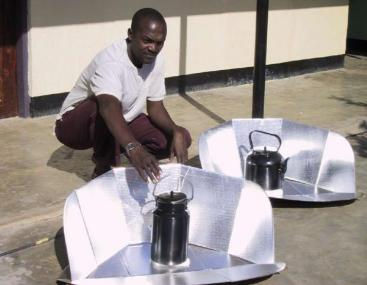 A solar cooking device with the black pan containing the water, and the reflecting panel increasing the efficiency of the pasteurisation process. Source: METCALF (2006).