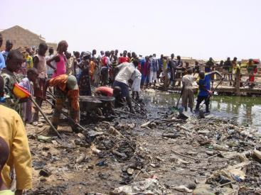 Due to absence of waste management, these community members in a semi-formal settlement in Kaolack, Senegal, are cleaning their water streamfrom solid waste. As access to clean water also has to do with dignity, this can also be seen as an act to restore their own dignity. (Source: R. TRATSCHIN)